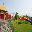 Big colorful children playground equipment in middle of park — Foto de Stock