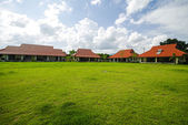 Red painted barns behind a green field of grass in the Thailand — Stock Photo