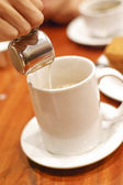 Man's hand pouring milk in white cup of coffee in cafe — 图库照片