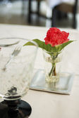 Dinning table set with red flower — Stock Photo