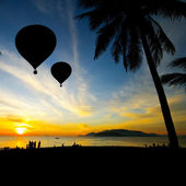 Balloon on Tropical beach with people in silhouette — Stock Photo