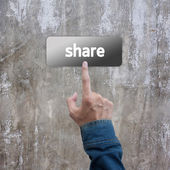 Press hand with jeans jacket on share botton concrete wall — Stock Photo