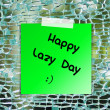 Happy lazy day on sticky paper background broken glass — Stock Photo