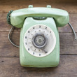 Green vintage telephone on brown wood desk background — Stock Photo #44322745