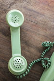 Green vintage telephone on brown wood desk background — Foto de Stock