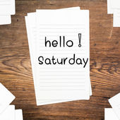 Hello Saturday on paper and wood table desk — Stock Photo