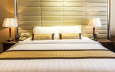 Bed in a hotel room at night — Stock Photo