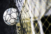 A soccer ball stuck on the net behind goal  — Stock Photo