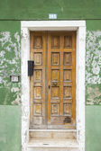 Old vintage wood door with old green wallpaper — Stock Photo