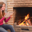 The girl is sitting alone near the fireplace and holds in hands the e-book tablet — Stock Photo