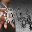 Businessman hand shows cogs - Stock Photo
