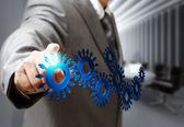 Ponto de mão de homem de negócios engrenagens ícones na sala de diretoria — Foto Stock