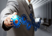 Business man hand point cogs icons in board room — Stock Photo