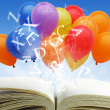 Open book with fancy balloons and text - Stock Photo
