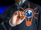 Mano con una penna disegno lampadina e globo — Foto Stock