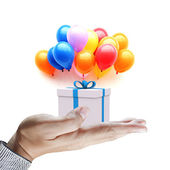 Hands holding gift in package with blue ribbon and colorful ball — Stock Photo