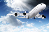 3d large passenger plane flying in the blue sky — Stock Photo