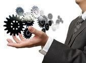 Empresário mostra a engrenagem para o sucesso no fundo branco — Foto Stock