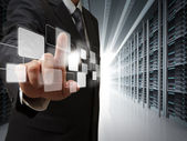 Business man point virtual buttons in server room — Stockfoto