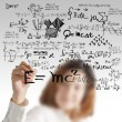Female draws maths and science formula - Stock Photo