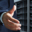 Business man offers handshake in server room - Stock Photo