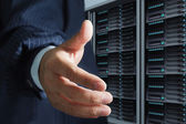 Business man offers handshake in server room — Stock Photo