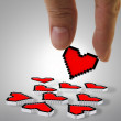 Fingers picking up pixel heart icon — Stock Photo