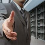 Businessmen offer hand shake in a technology data center — Stock Photo #13081876
