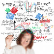 Female teacher writing various high school maths and science for - Stock Photo