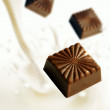 Chocolate blocks falling into milk — Stockfoto