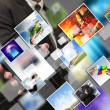 Business hand shows touch screen mobile phone with streaming ima — Stock Photo #13121571