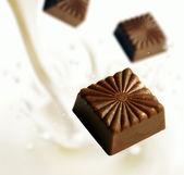 Chocolate blocks falling into milk — Stock Photo