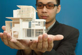Man holding a model of a house in his hands. — Stock Photo