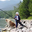 A boy with a fishing pole and a dog — Stock Photo