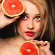 Woman holding in the hands of two grapefruits — Stock Photo
