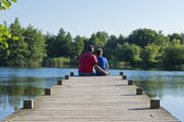 Father and Son on a Wooden Pier on a Pond — Stock Photo