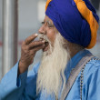 Aged Sikh eating Offering — Stock Photo