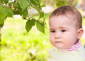 Thoughtful child near a blossoming cherry — Stock Photo