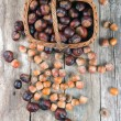 Chestnuts and acorns on a wooden background — Stock Photo