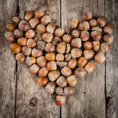 Acorns forming a heart on a wooden background — Stock Photo