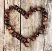 Chestnuts forming a heart on a wooden background — Stock Photo