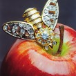 Still life with red apple and golden bee brooch — Stock Photo