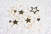 Sterne und glasperlen auf weißem sand — Stockfoto