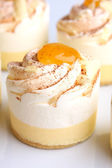Little cream cakes with vanilla and white chocolate flavor and orange jelly — Stock Photo