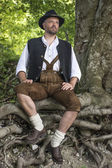Seated man in traditional Bavarian costumes in forest — Stock Photo