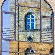 Stock Photo: Mirroring of old house in window