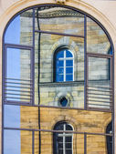 Mirroring of a old house in window — Stock Photo