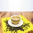 Coffee with beans on serviette — Stock Photo