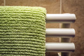 Green towel on radiator — Stock Photo
