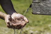 Thirsty Hands taking water from well — Stock Photo